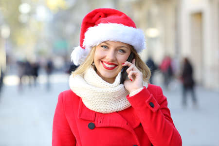Front view portrait of a happy woman talking on phone looking at you on christmas in the street Stock Photo