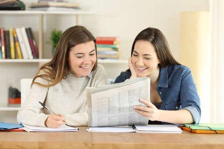 Dos estudiantes felices hablando de noticias de periódicos en casa