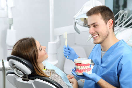 Happy dentist explaining teeth brushing procedure to a patient in a office Stock Photo