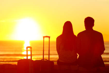Back view backlight silhouette of a couple of travelers looking at sun on vacation travel 스톡 콘텐츠