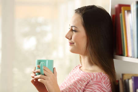 Side view portrait of a relaxed woman holding a coffee cup looking away at home Imagens