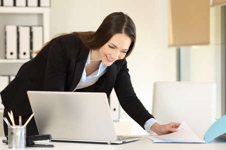 Happy businesswoman comparing documents online on a desk at office
