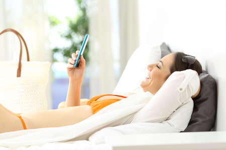 Relaxed hotel guest using a phone on vacations lying on a bed of a room on summer vacations Stock Photo
