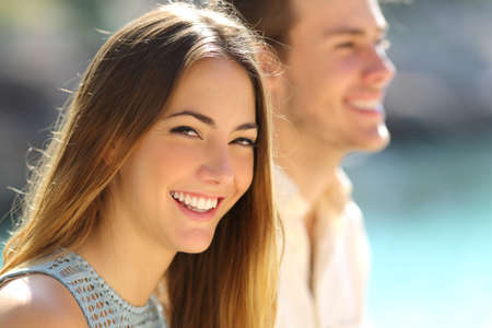 Happy woman smiling with perfect teeth looking at you beside her partner on the beach