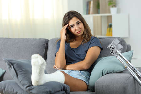 Sad disabled girl complaining looking at camera sitting on a couch in the living room at home Stockfoto