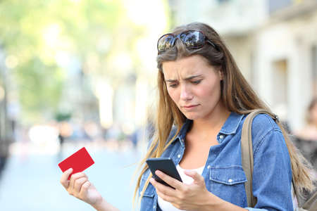 Worried girl having online payment problems with a smart phone in the street Stock fotó