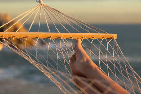 Close up of a woman legs resting on a hammock on summer vacation at sunset Stock Photo