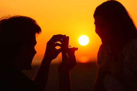 Backlight silhouette of a marriage proposal at sunset with sun in background
