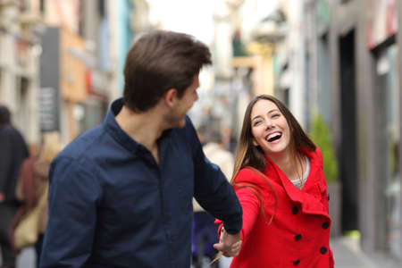 Happy couple running together in the street in winter