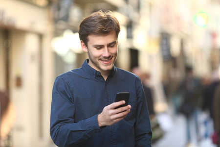 Smiley man checking smart phone content walking in the street of an old town