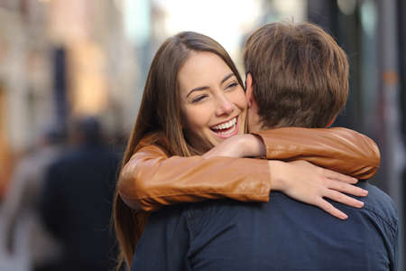 Happy couple of friends meeting and hugging in the street