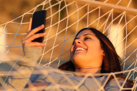 Happy girl resting on a hammock using a smart phone on vacation at sunset