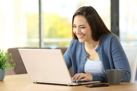 Happy woman writing in a laptop on a desk at home Stock Photo