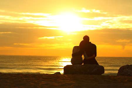 Retroilluminazione retroilluminata di una silhouette di coppia che si incontra al tramonto sulla spiaggia