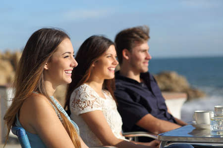 Side view portrait of three happy friends watching the beach in a coffee shop in a sunny day on vacation Stock Photo