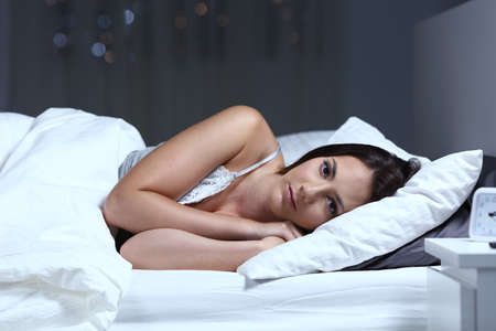 Serious insomniac woman looking at camera lying on the bed in the night at home