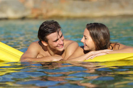 Couple flirting floating on an inflatable bed on the beach on summer vacation