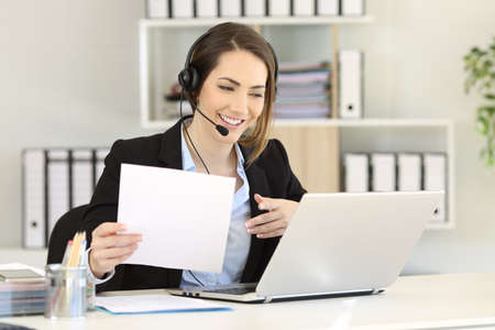 Telemarketer attending a call consulting online information in a laptop at office Stock Photo