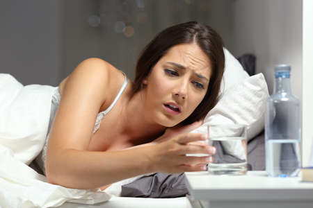Thirsty woman reaching a glass of water lying on the bed in the night at home