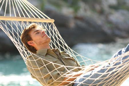 Relaxed man sleeping on a hammock on summer vacation on the beach