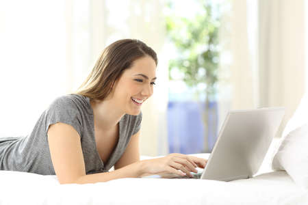 Happy lady using a laptop searching online on the bed at home Stock Photo