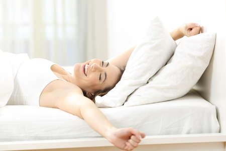 Happy woman waking up stretching arms lying on a bed in the morning at home Stock Photo