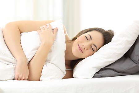 Happy woman sleeping embracing a pillow lying on a bed at home
