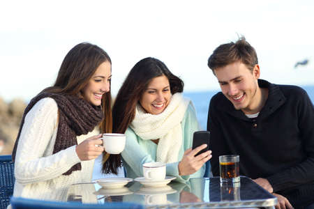 Three happy friends watching media content in a smart phone in a bar in winter