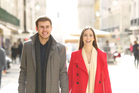 Front view portrait of a happy couple taking a walk in winter in the street Stock Photo