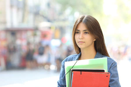 Portrait of a serious student holding folders walking looking away in the street