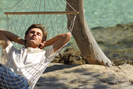 Relaxed man resting on a hammock on the beach on summer vacation Stock Photo