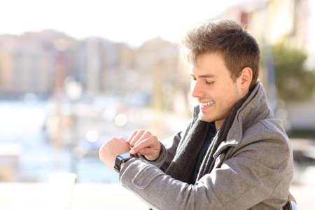 Happy man checks smartwatch in a coffee shop in winter Stock Photo