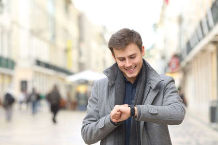 Happy man checking his smart watch in the street in winter