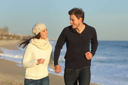 Happy couple running together towards camera on the beach in winter