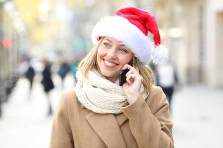 Happy woman wearing a santa hat talking on phone on christmas on the street Zdjęcie Seryjne