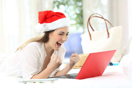 Excited woman with a laptop on christmas holidays lying on a bed in an hotel room Stock Photo