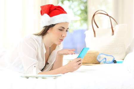 Woman on christmas holidays having a video call lying on a bed in an hotel room