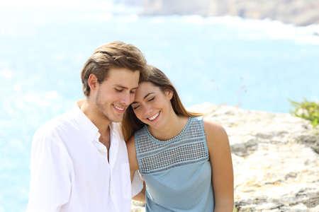 Happy couple flirting on vacation travel on the beach