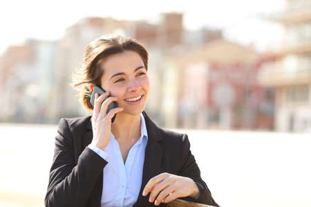 Happy businesswoman talking on phone sitting on a bench in a park Stock Photo