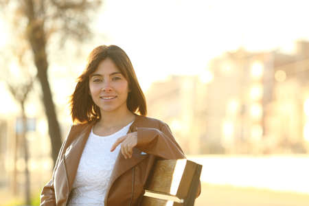 Happy confident woman looking at camera sitting on a bench in a park