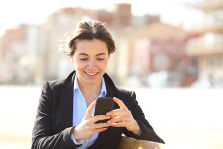 Happy busineswoman texting on smart phone sitting on a bench in a park