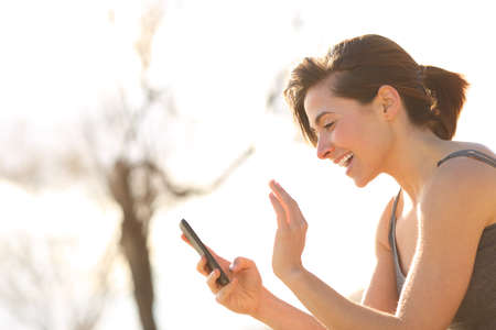 Profile of a happy woman having a video call on a smart phone outdoors