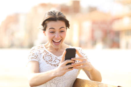 Excited girl reading amazing news on a smart phone sitting on a bench in a park