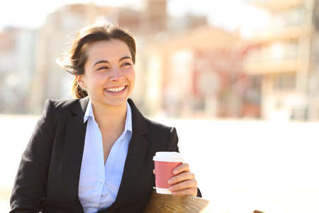 Happy businesswoman looking away at coffee break sitting on a bench in a park Stock Photo
