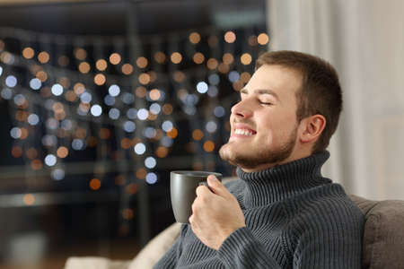 Happy man enjoying coffee in the night sitting on a couch in the living room at home Stock Photo
