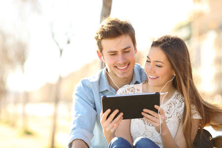 Happy couple sharing online tablet content sitting on a bench in a park