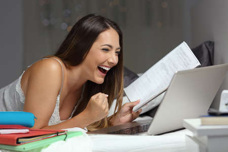 Excited student reading good news online in a laptop lying on a bed in the night at home
