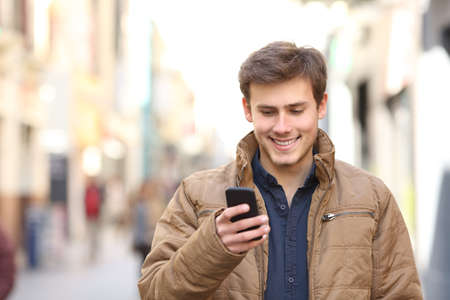 Front view of happy man texing on smart phone in winter in the street