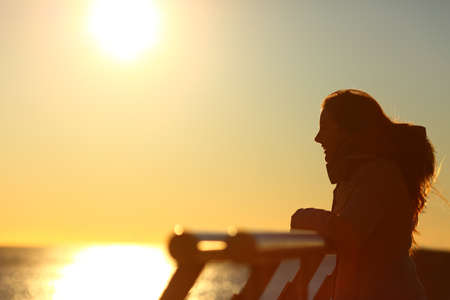 Side view portrait of a silhouette of a woman looking at horizon at sunset on a bridge over the sea