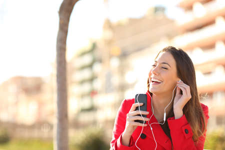 Happy woman singing and listening to music from a smartphone sitting on a bench in a park
